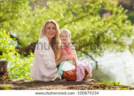 Happy young mother and child having rest near the river - stock photo