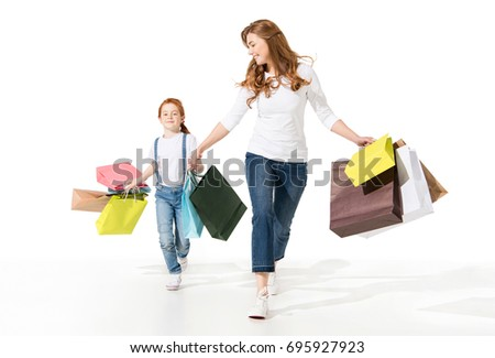 happy young mother and cute little daughter holding shopping bags and walking together isolated on white