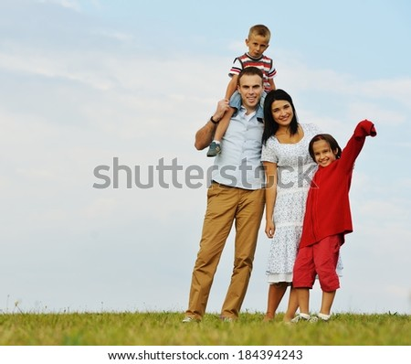 Happy young mother and father with two sons in nature