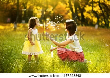 Happy young mother and her daughter blowing soap bubbles in autumn - stock photo