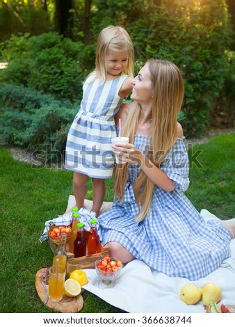Happy young mother and her daughter having picnic in summer park - stock photo