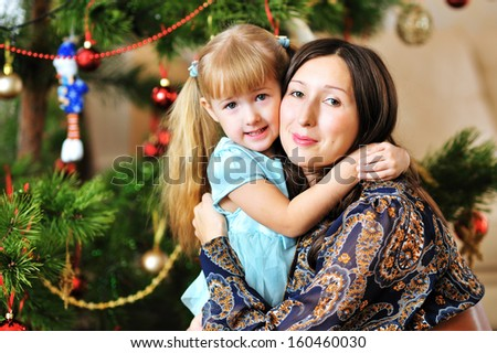 Happy young mother and her daughter hugging near Christmas tree.