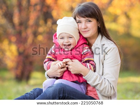 happy young mother and her daughter kid have fun sitting at fall background
