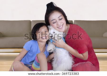 Happy young mother and her daughter playing and hugging a maltese dog at home