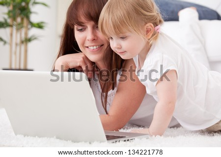 Happy young mother and her  daughter using a laptop - stock photo