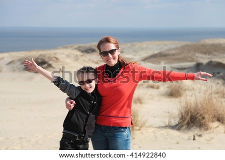 Happy young mother and her funny son in sunglasses on the seashore - stock photo