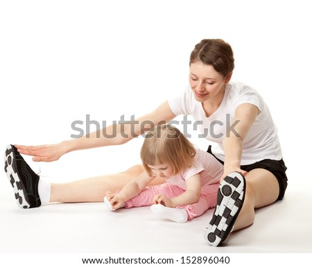 Happy young mother and her little daughter doing sport exercises; white background - stock photo