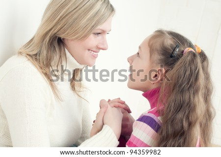 Happy young mother and her little daughter looking at each other and holding each other by the hands