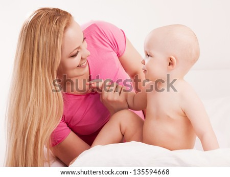 happy young mother and her one year old baby in bed at home - stock photo