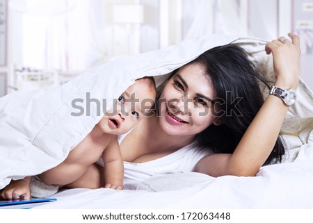 Happy young mother and her one year old daughter in bed at home - stock photo