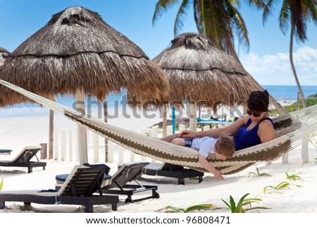Happy young mother and her son in a hammock on a Caribbean beach - stock photo