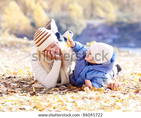 happy young mother and her son spending time outdoor in the autumn park  (focus on the woman) - stock photo
