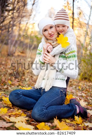 happy young mother and her son spending time outdoor in the park (focus on the woman)