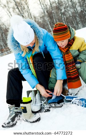 happy young mother and her son tightening laces and getting ready to go ice-skating