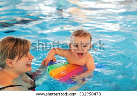 Happy young mother and little baby swimming in indoor pool. Healthy childhood and growth of children - stock photo