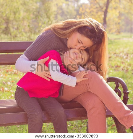 Happy young mother and little girl have fun in the park. Family lifestyle, autumn season.