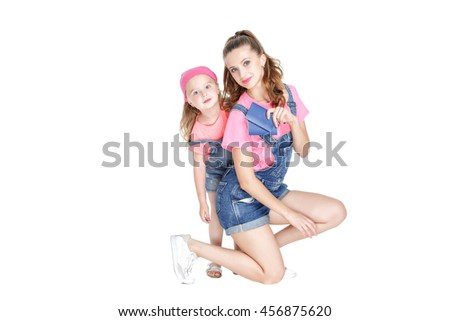 happy young mother and lovely daughter is going on a trip. smiling woman and child hold two passports. isolated on white background - stock photo