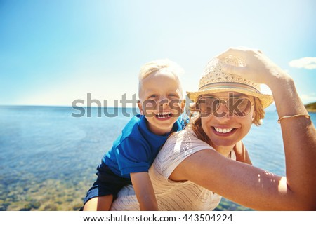 Happy young mother and son on a tropical beach with the laughing little boy getting a piggy back ride on her back - stock photo