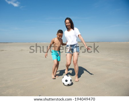 Happy young mother and son playing football on the beach - stock photo