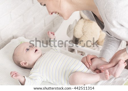 Happy young mother bending above her little baby in sleepers lying  on a changing table. Preparing baby to change a diaper - stock photo