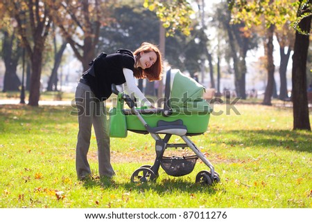 Happy young mother carrying baby in autumn park - stock photo
