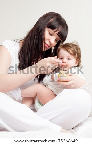 happy young mother feeding her baby with yogurt (focus on the baby)