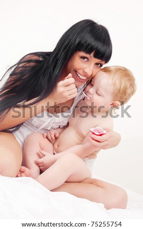happy young mother feeding her baby with yogurt (focus on the mother)