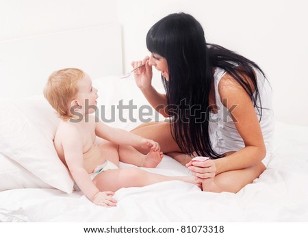 happy young mother feeding her baby with yogurt on the bed at home - stock photo