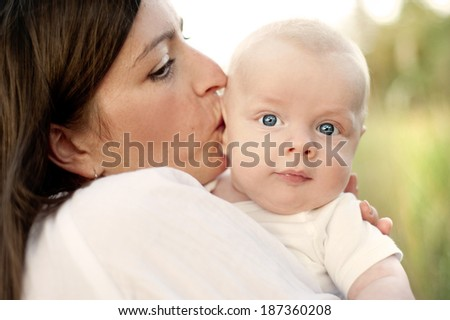 Happy young mother having fun with her baby son in nature