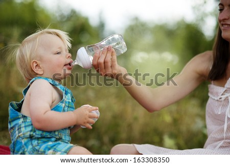 Happy young mother having fun with her son in nature
