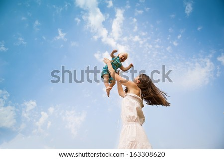 Happy young mother having fun with her son in nature - stock photo