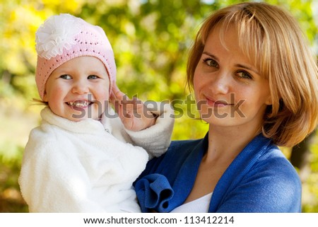 Happy young mother holding a his little daughter - stock photo