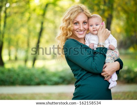 Happy young mother holding her baby