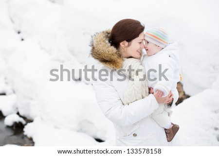 Happy young mother holding her baby in a snowy winter park - stock photo