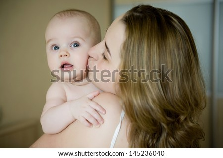 Happy young mother holding her newborn baby boy skin to skin and kissing him