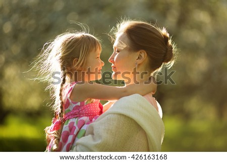 Happy young mother holding his baby daughter - stock photo