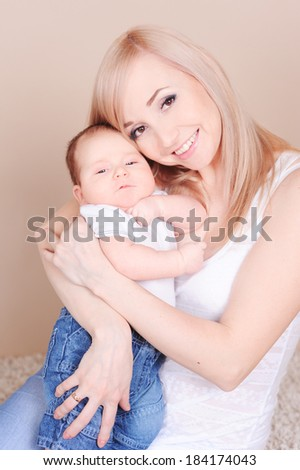 Happy young mother holding little baby. Smiling woman with newborn child over beige. Motherhood