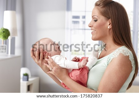 Happy young mother holding newborn baby girl in arms, smiling to her.