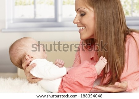 Happy young mother holding tiny newborn baby.