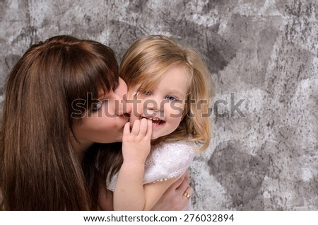 happy young mother kissing her laughing little daughter on gray wall background - stock photo