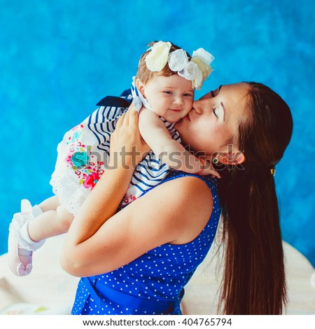 happy young mother kissing her little baby - stock photo