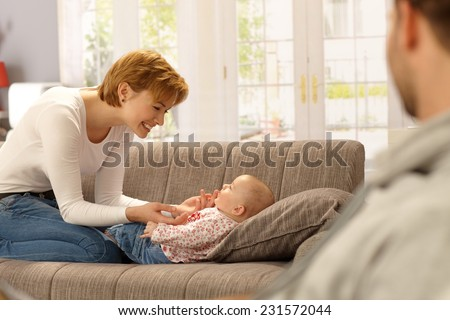 Happy young mother kneeling on sofa, playing with lying baby. Side view, - stock photo