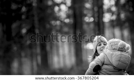Happy young mother outside in winter nature holding her baby in her lap looking at him happily as he looks up in the air with blurred trees in background and copy space to the left side of the image. - stock photo