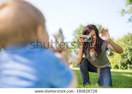 Happy young mother photographing son through camera in park - stock photo