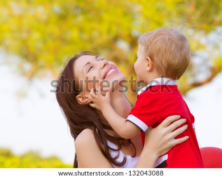 Happy young mother playing game with cute little son outdoors in spring time, cheerful child with mom having fun on backyard, woman with small kid resting in the park in sunny day - stock photo