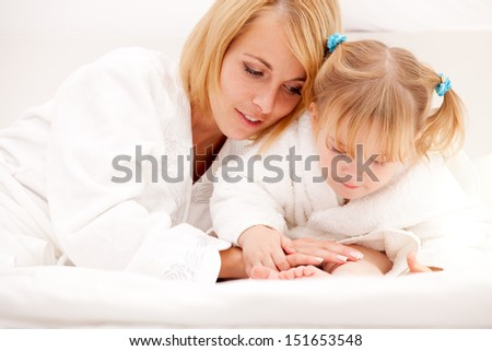 happy young mother playing with daughter on bed at home - stock photo