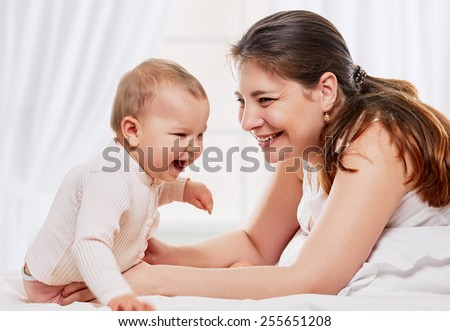 happy young mother playing with her baby daughter on the bed at home