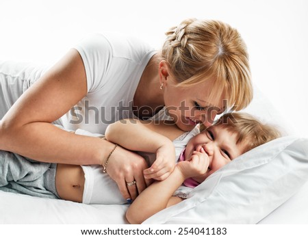 happy young mother playing with her daughter on the bed on white