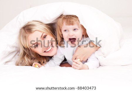 happy young mother playing with her daughter under the blanket on the bed at home (focus on the woman) - stock photo