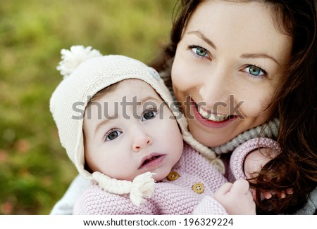 Happy young mother relaxing with her little daughter in golden and colorful autum nature - stock photo